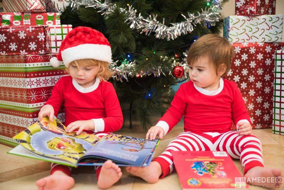 小朋友坐在聖誕樹下看書