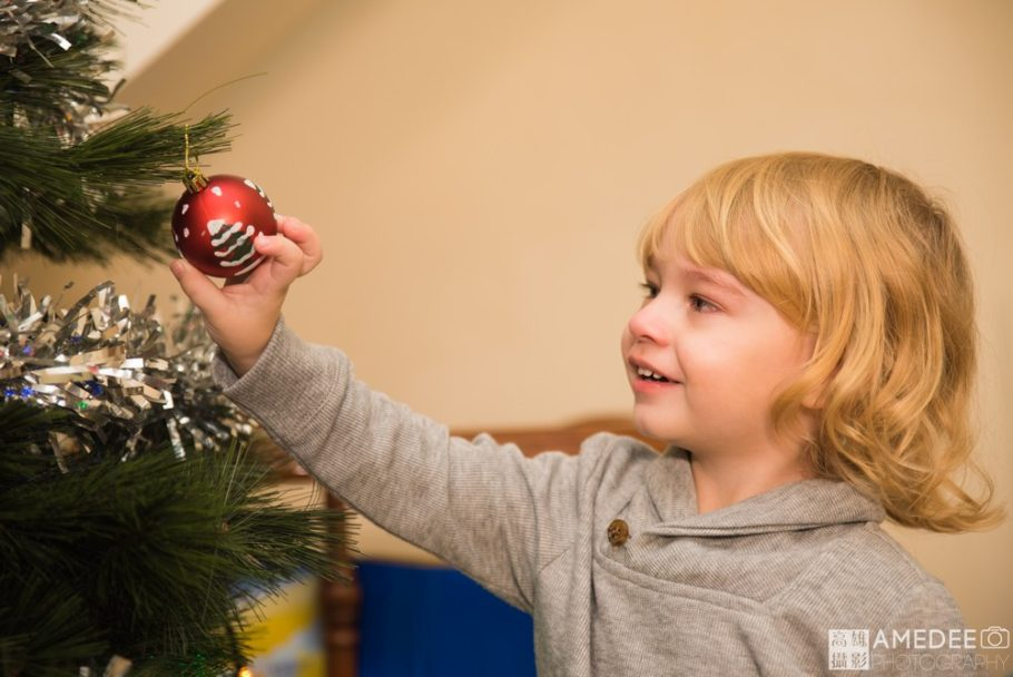 小朋友伸手摸聖誕樹裝飾