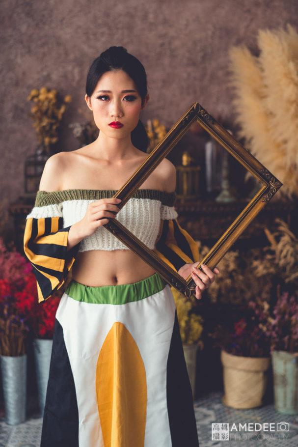 服裝模特兒拿著相框擺拍
