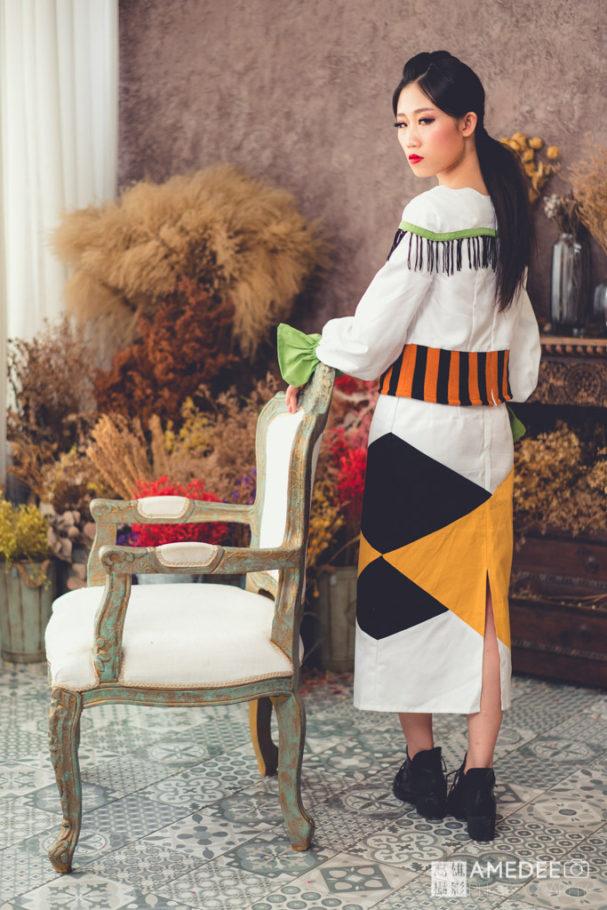 服裝模特兒靠著椅子擺拍