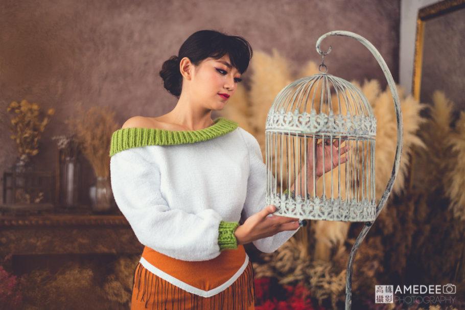 服裝模特兒拿著鳥籠擺拍
